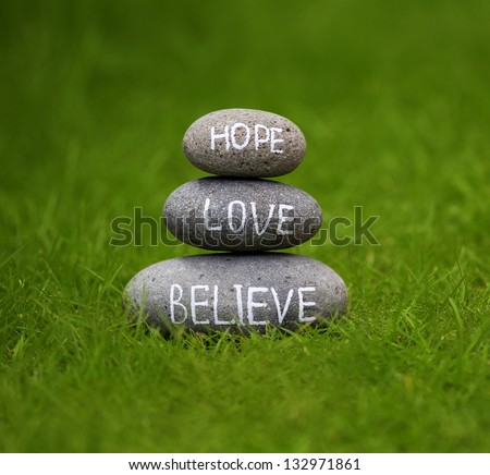 Believe, hope and love rock in the grass - stock photo