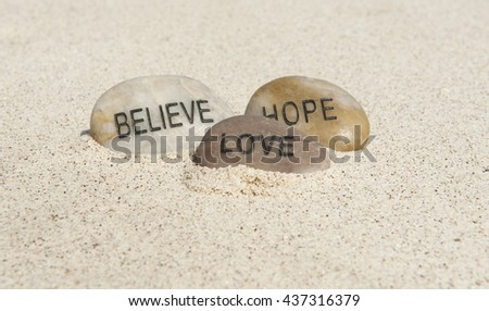 Believe, hope and love rocks on a white sand beach