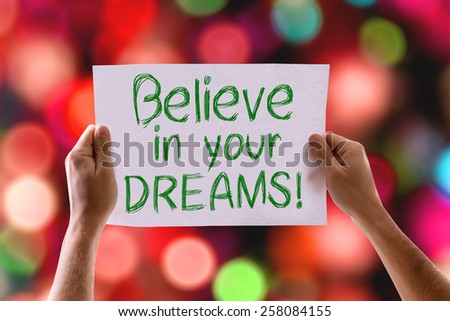 Believe in your Dreams card with colorful background with defocused lights - stock photo