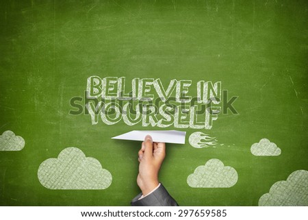 Believe in yourself concept on green blackboard with businessman hand holding paper plane - stock photo