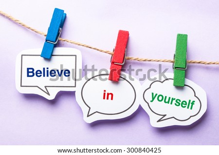 Believe in yourself paper bubbles with clip hanging on the line against purple background. - stock photo