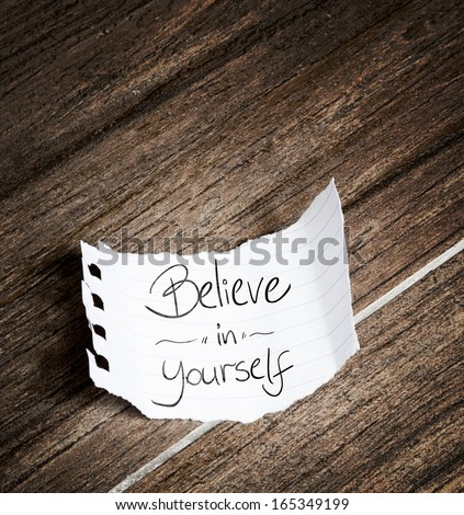 Believe in yourself written on the paper on a wood background - stock photo