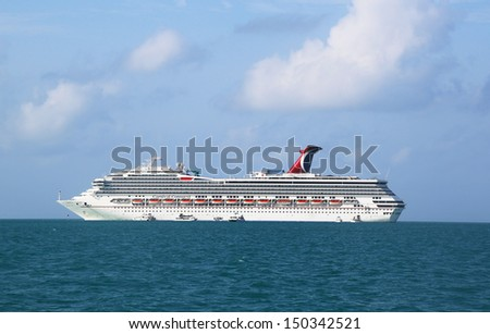 BELIZE- JUNE 13:  Carnival Conquest Cruise Ship anchors near Belize City and ready to tender visitors to the port on June 13, 2013.  Carnival Conquest has capacity of 2974 passengers and crew of 1150  - stock photo