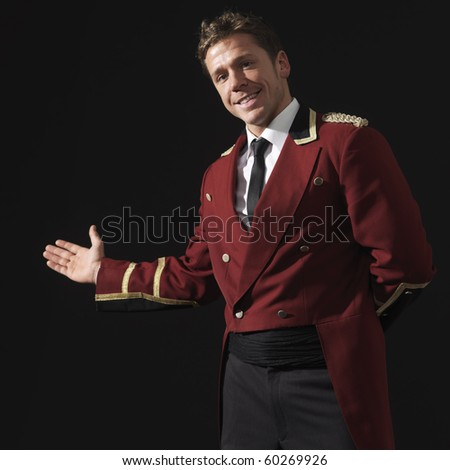 Bell hope gesturing to enter. Hotel staff. Square format. - stock photo