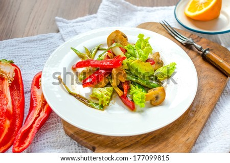 Bell pepper, avocado, mushrooms and leek salad on white plate