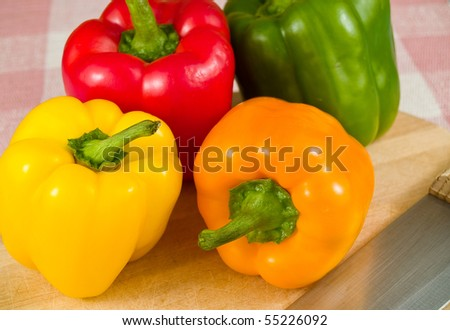 Bell Peppers on a Wooden Cutting Board with Knife - stock photo