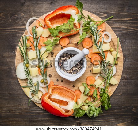 bell peppers, various unground pepper, chopped carrots, potatoes and herbs on a cutting board on wooden rustic background top view - stock photo