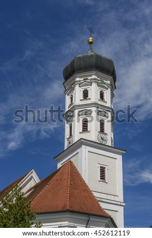 Bell tower of a Bavarian church against the blue sky