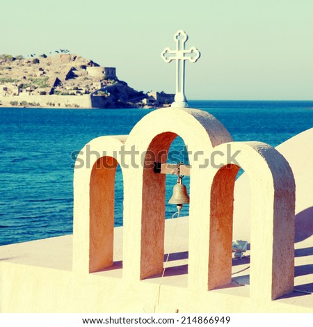 bell tower of a little classical orthodox Greek church with view of Mediterranean sea and Spinalonga island(Crete,Greece). Instagram effect, square image - stock photo