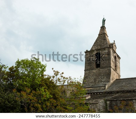 Bell tower of Notre-Dame-de-la-Major church over the trees in Arles (Provence, France) - stock photo