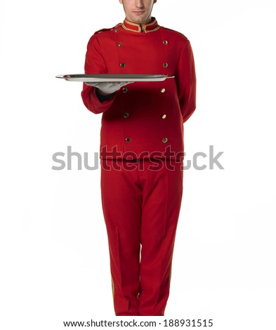 Bellboy with a tray dressed in red.  - stock photo