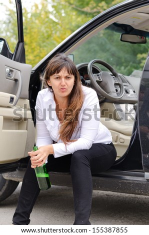 Belligerent drunk woman sitting in the open door of her car on the sill glaring at the camera as she clutches her bottle of alcohol - stock photo