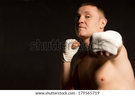 Belligerent young boxer throwing a punch as he eyes up his opponent with an intense expression, focus to his face on a dark background with copyspace - stock photo