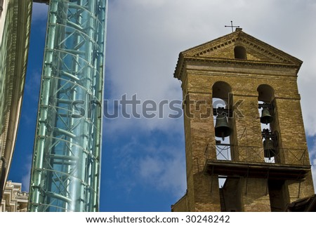 Belltower Of A Medieval Church And A Modern Glass Elevator