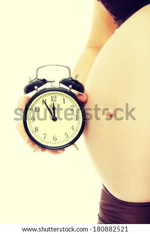 Belly of a pregnant woman with alarm clock - stock photo
