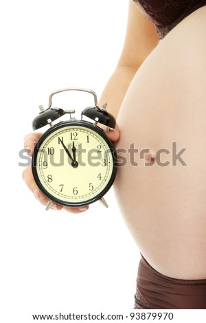 Belly of a pregnant woman with alarm clock, isolated on white - stock photo