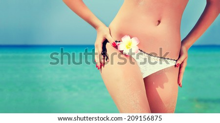 Belly of a young sexy woman standing at beach - stock photo