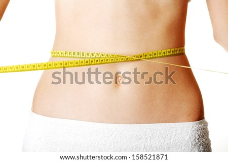 Belly of beautiful young female with measuring tape
