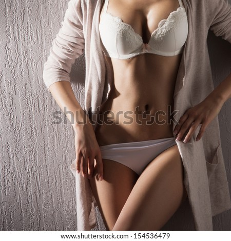 Belly of sexy woman in white lingerie - stock photo