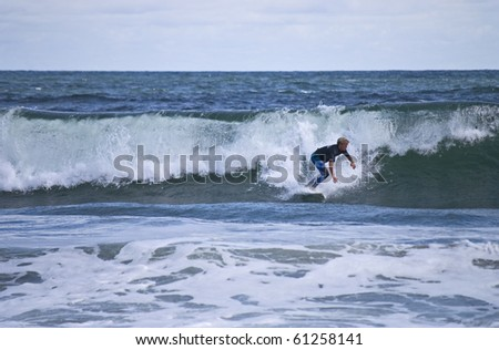 BELMAR, NJ - SEPTEMBER 18: Unidentified surfer catches a wave at The Foster's Belmar Pro Surfing contest on Sept. 18, 2010 in Belmar, NJ.
