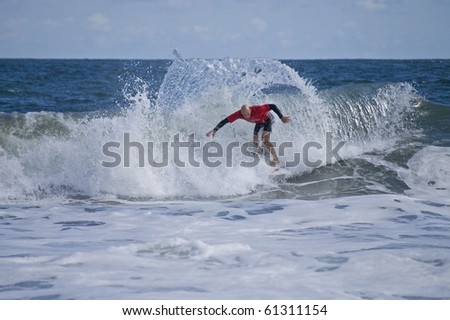 BELMAR, NJ - SEPTEMBER 18: Unidentified surfer catches a wave at The Foster's Belmar Pro Surfing contest on Sept. 18, 2010 in Belmar, NJ