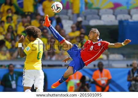 BELO HORIZONTE, BRAZIL - June 28, 2014: Marcelo of Brazil and Arturo Vidal of Chile during the 2014 World Cup Round of 16 game between Brazil and Chile at Mineirao Stadium. NO USE IN BRAZIL. - stock photo