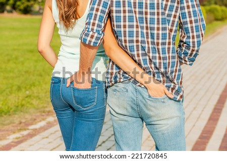 Belong to each other. Young loving couple holding their hands in the pockets of each others jeans while walking.  - stock photo