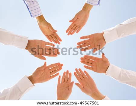 Below angle of circle of people hands with blue sky above - stock photo
