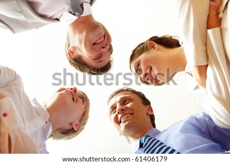 Below angle of happy business people looking at each other - stock photo