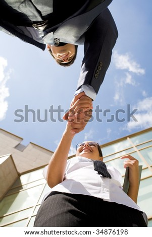 Below angle of successful partners handshaking after striking deal - stock photo