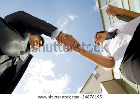 Below angle of successful partners handshaking after striking deal at meeting