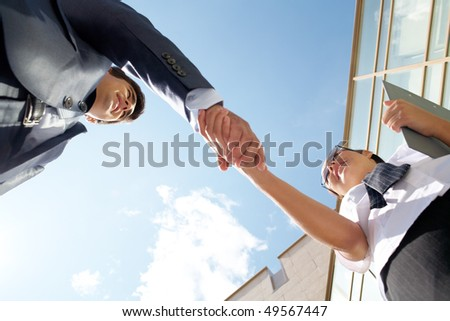 Below angle of successful partners handshaking after striking deal at meeting - stock photo