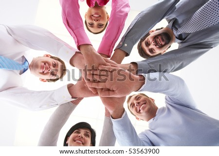 Below shot of smiling co-workers making pile of hands - stock photo