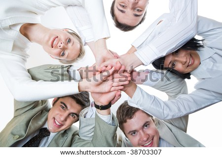 Below shot of smiling co-workers making pile of hands and looking at camera - stock photo