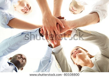 Below shot of smiling co-workers making pile of hands and looking at each other