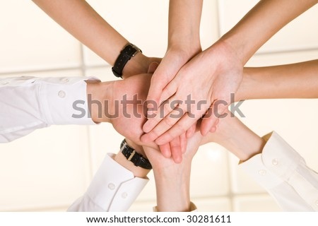 Below view of business partners? hands making pile as symbol of companionship and unity - stock photo