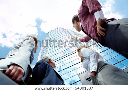 Below view of business partners pointing at modern office building against cloudy sky