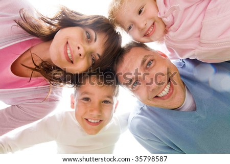 Below view of family looking at camera against light sky - stock photo