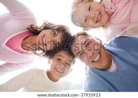 Below view of family looking at camera against light sky