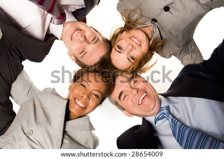 Below view of four partners looking at camera with their heads next to each other