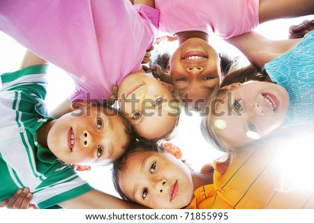 Below view of happy children embracing each other and smiling at camera - stock photo