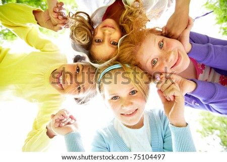 Below view of happy girls standing head by head to each other and holding by hands - stock photo