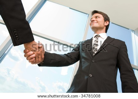 Below view of happy man handshaking with partner after striking business deal