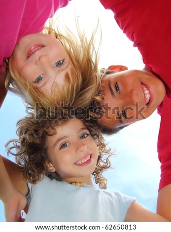 Below view of happy three children embracing hug each other smiling camera - stock photo
