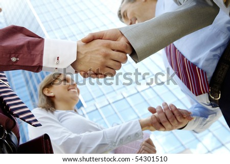 Below view of rows of happy partners handshaking outdoors on background of modern building - stock photo