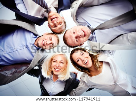Below view of several happy business partners looking at camera while embracing each other - stock photo