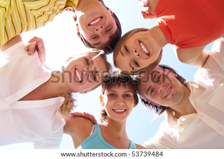 Below view of several happy friends standing head by head to each other
