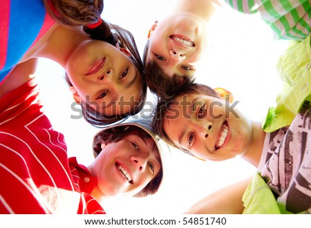 Below view of several happy teens standing head by head to each other - stock photo
