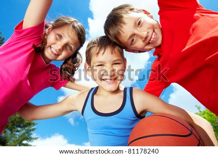 Below view of three little friends looking at camera and smiling - stock photo