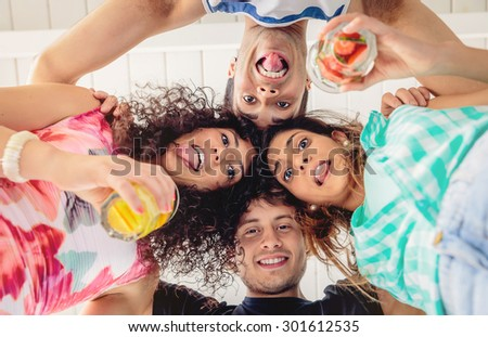 Below view of young happy people with their heads together and holding healthy drinks having fun in a summer party. Young people lifestyle concept. - stock photo